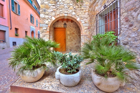 sirmione: Stone pots with palms in front of entrance to typical italian house on narrow cobblestone street in town of Sirmione, Italy