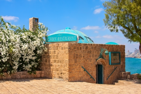 ancient israel: JAFFA - JULY 03:  Exterior of small restaurant situated above the sea in an ancient 600 year old building with spectacular view of Tel Aviv shoreline and is higly popular with tourists visiting old Jaffa, Israel on July 03, 2009. Editorial