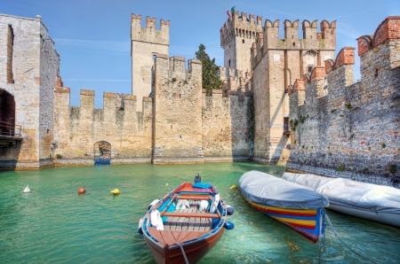 sirmione: SIRMIONE - APRIL 01: Boats in front of famous medieval Scaglieri castle located on Lake Garda in town of Sirmione, Northern Italy on April 01, 2012. Editorial
