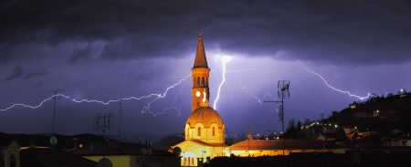 alba: Panoramic view on lightning over Alba and surrounding hills during thunderstorm in northern Italy