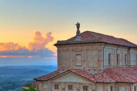 Statue of Jesus Christ on the church roof and hills of Langhe on background at sunset under beautiful evening sky in Piedmont, Northern Italy  photo