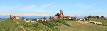 Panorama of small typical italian town with medieval castle, hill, vineyards and mountains on the background in Piedmont, Northern Italy