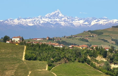Small village on the hill with vineyards and Monviso alpine mountain peak covered with snow on background in Piedmont, Italy