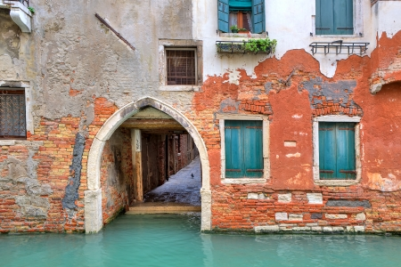 Narrow canal and facade of old red brick house with closed shutters in Venice, Italy  photo