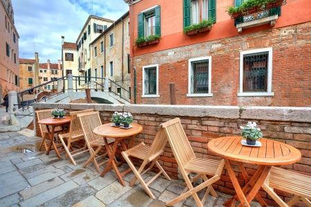 Wooden tables on narrow street among typical colorful houses and small bridge in Venice, Italy  photo