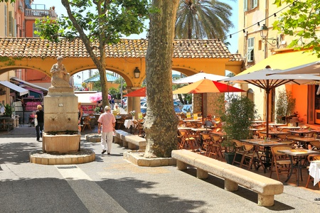 MENTON - JUNE 13: Little square with bars and restaurants in the shade of trees and  small statue in the center of a town on French Riviera (Cote d