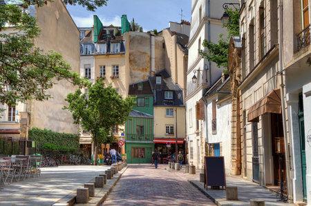 パリ、フランスの伝統的なパリの建物の間で狭い石畳の通りを見る