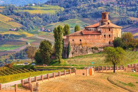 Vista del castello abbandonato e vigne autunnali delle Langhe in Piemonte, Nord Italia