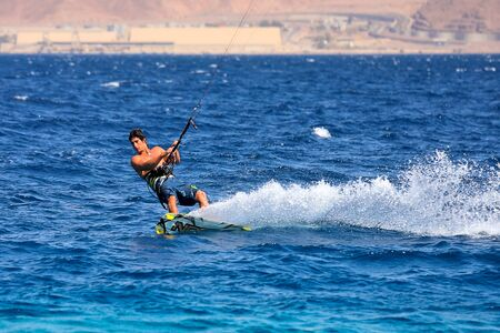 EILAT, ISRAEL - MARCH 31  Unidentified kitesurfer glides on water surface during local competition in popular tourist town of Eilat located on the shores of Red Sea in Israel on March 31, 2010