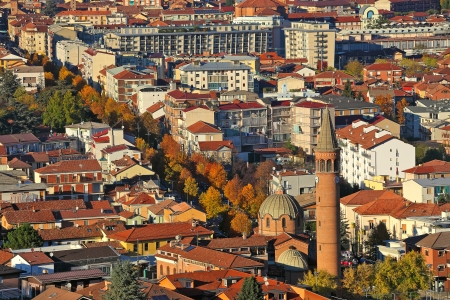 Urban buildings with red roofs and church lit by last rays of setting sun at evening in Alba, Italy  view from above   photo