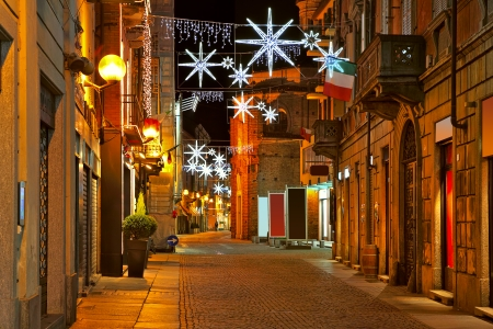 Old city central street with illuminations and decorations for Christmas and New Year celebrations at night in Alba, Italy  스톡 콘텐츠