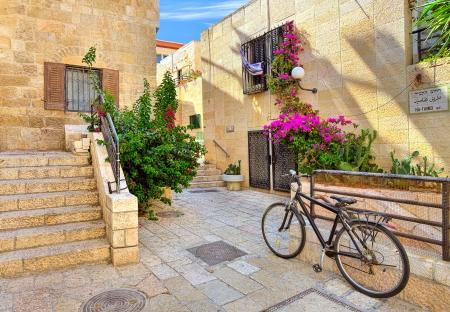 古い都市のエルサレム、イスラエル共和国のユダヤ人地区の典型的な投石家の間で狭い通りに自転車