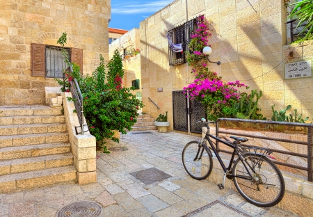 Bicycle on narrow street among typical stoned houses of jewish quarter in Old City of Jerusalem, Israel  Standard-Bild