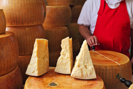 parmesan cheese: Three pieces of cheese on top of whole Parmesan wheel as cheesemaker cuts another wheel on background at International Cheese Festival in Bra, Northern Italy  Editorial