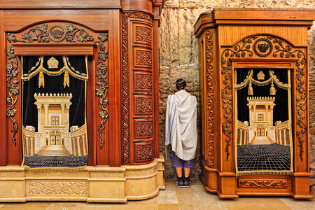 tora: JERUSALEM - AUGUST 21  Prayer in Cave Synagogue between two wooden cabinets with Torah scrolls  Cabinets located in the cave which is a part of Western Wall - Judaism holy place in Jerusalem, Israel on August 21, 2013