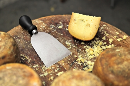Special knife and famous italian cheese pecorino on small wooden table