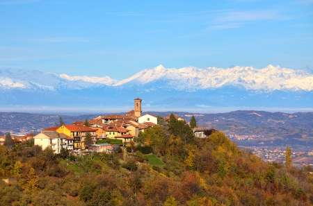 View of small town on top of the hill surrounded by autumnal trees and snowy peaks of Alps on background in Piedmont, Northern Italy  photo