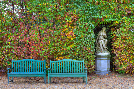 racconigi: Two wooden benches on alley in front of bushes with lush colorful foliage and old sculpture in autumn Racconigi park, Italy