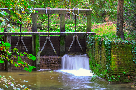 racconigi: Wooden dam, small waterfall and forest streem at Racconigi park in autumn in Piedmont, Northern Italy