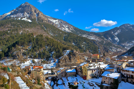 alpes: View of small french town of Tende among mountains under blue sky in winter