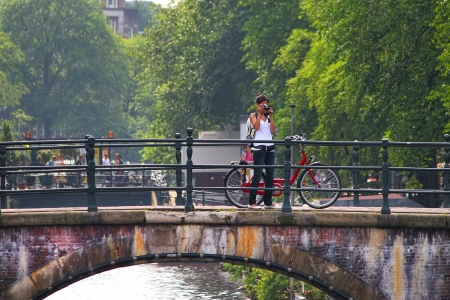 AMSTERDAM - JULY 17  Unidentified woman take pictures standing near red city bicycle on the bridge over canal Bicycles are the most used mode of transport and very popular with tourists and locals in Amsterdam, Netherlands on July 15, 2007  Stock Photo - 23492924