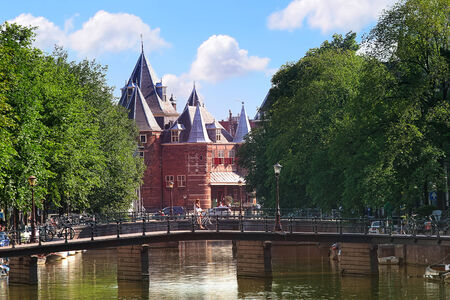 amstel river: Typical city view of bridges aver Amstel river and red brick church on background in Amsterdam, Netherlands