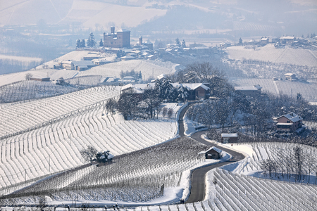 Narrow road through hills and vineyards covered with snow towards small village in Piedmont, Northern Italy  photo