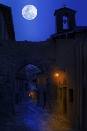 alpes maritimes: Night view of narrow street between old houses under the sky with full moon in town of Tende, France  Stock Photo