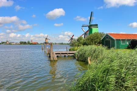 Wooden windmills along river under beautiful blue sky with white clouds in famous dutch village of Zaanse Schans  photo