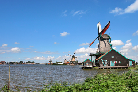 Wooden windmills along river under beautiful blue sky with white clouds in typical dutch village of Zaanse Schans  photo