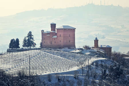 Medieval castle on the hill covered with snow in small italian town in Piedmont, Northern Italy