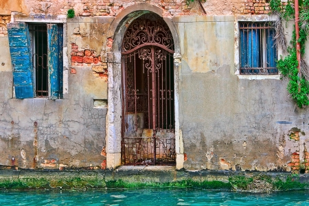 Facade of old abandoned house with metal gate, cracked brick walls and wooden shutters on small canal in Venice, Italy  photo