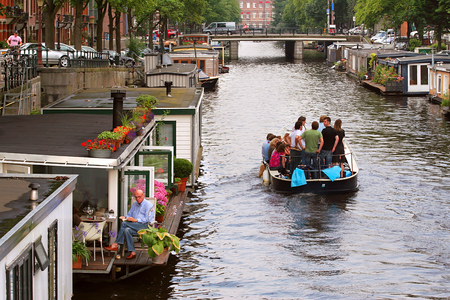 house float on water: AMSTERDAM - JULY 15  Boat with tourists passing by houseboats on city canal  Houseboats are high demand very popular and common form of housing in Amsterdam, Netherlands on July 15, 2007  Editorial