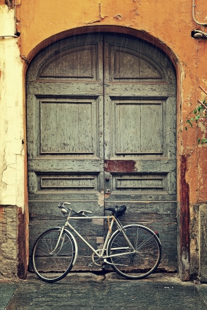 Vertical oriented image of bicycle leaning against old wooden door at the entrance to house on rainy day in Alba, Italy  Stock Photo