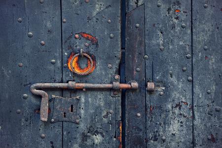 door bolt: Closeup image of old wooden door with metal knob and rusty bolt