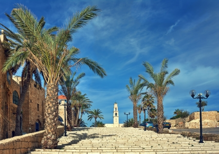 yaffo: Stone stairs among palms under beautiful blue sky with white clouds leading towards St  Peter Stock Photo