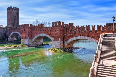 across: Famous red brick Castelvecchio bridge across Adige river in Verona, Italy