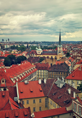 praha: Vertical oriented image of typical buildings with red roofs in old city under cloudy sky in Prague, Czech Republic  toned