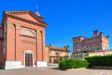 Red brick church and medieval castle on the hill under blue sky in town of Grinzane cavour in Piedmont, Northern Italy