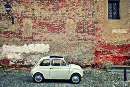 saluzzo: Small old car stand on cobbled street against red brick wall with lamppost in Saluzzo, Northern Italy