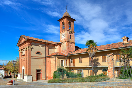 cavour: Old red brick catholic church on town square under beautiful blue sky in small town of Grinzane Cavour in Piedmont, Northern Italy