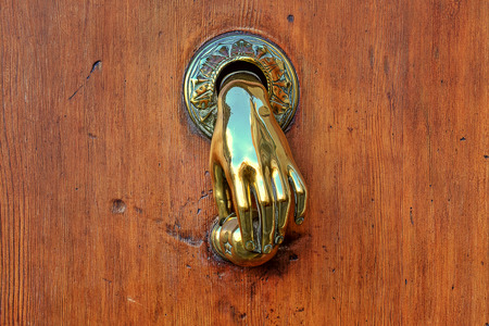 Hand shaped golden door knob on brown wooden door on Valencia, Spain  photo