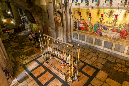 sepulcher: JERUSALEM  ISRAEL - AUGUST 21, 2013  Stone of Anointing  aka Stone of Unction  and mosaic icon on the wall at the entrance to Holy Sepulcher church designate the place where Jesus