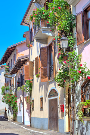 small town: Vertical oriented image of typical italian house with balcony and blinds decorated with flowers in town of La Morra in Piedmont, Northern Italy  Stock Photo