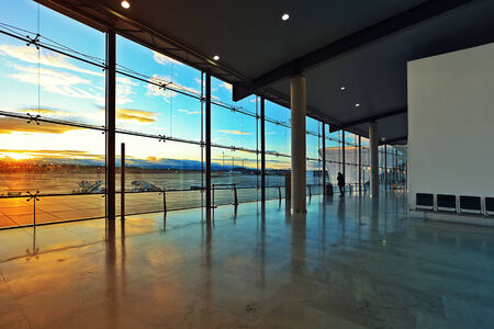 Departures hall and big window with beautiful view on airport field at sunset in Valencia, Spain