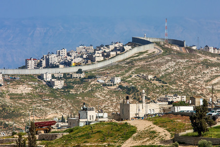 israeli: Small village and palestinian town on the hill behind israeli separation barrier on the West Bank in Israel
