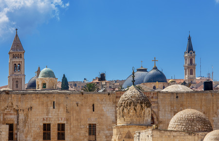 Belfries and domes of christian churches and minarets of mosques under blue sky in Jerusalem, Israel  photo