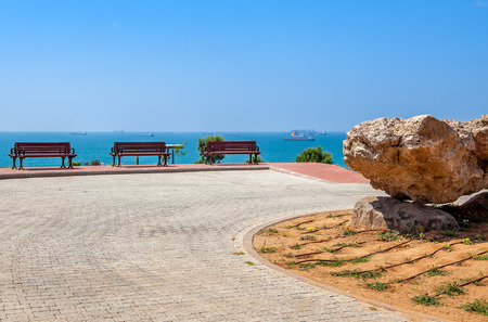 yam israel: Large stone and benches in urban park with beautiful view on Mediterranean sea in Ashdod, Israel  Stock Photo