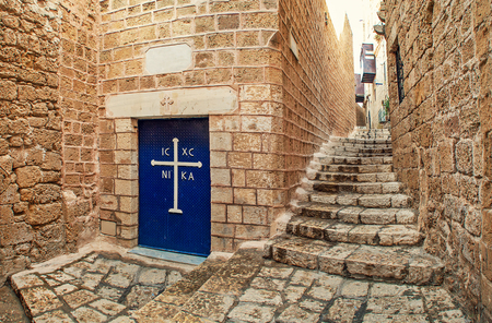 yafo: Metal door with white cross at the entrance to small church and narrow stone streets in Jaffa, Israel  Stock Photo