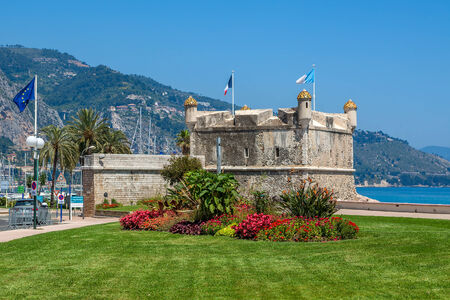 menton: Green grass with flowers on promenade and medieval fortress in Menton, France  Stock Photo
